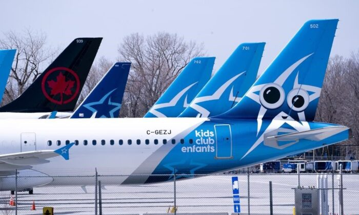 Tails of Air Transat and an Air Canada aircraft are seen on the tarmac at Montreal-Trudeau International Airport, in Montreal, on April 8, 2020. (Paul Chiasson/The Canadian Press/File photo)