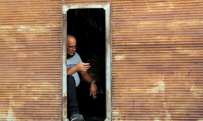 A man checks his phone as telephone and internet connections were knocked out in a nationwide failure, in Havana, Cuba, on Feb. 12, 2021. (Stringer/Reuters)
