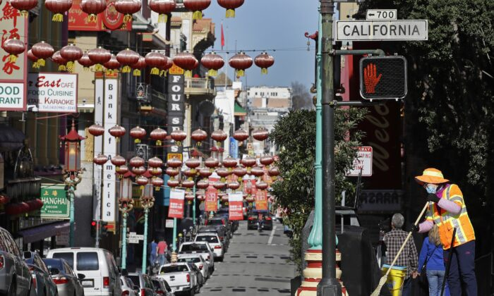 A masked worker cleans a street in the Chinatown district in San Francisco, Calif., on Jan. 31, 2020. (Ben Margot/AP Photo)