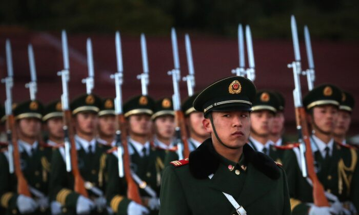 A paramilitary police officer stands guard during a flag-lowering ceremony at Tiananmen Square in Beijing on Nov. 13, 2012. (Feng Li/Getty Images)