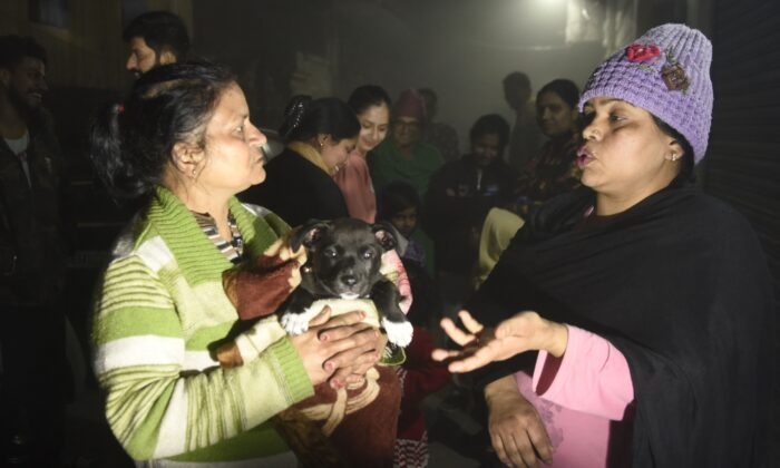 Residents—one holding a puppy—speak on a street in Amritsar after leaving their homes as tremors shook the city in Punjab State north-western India following a powerful earthquake in Tajikistan of a magnitude of 5.9 according to the United States Geological Survey (USGS), late Feb. 12, 2021. (Narinder Nanu/AFP via Getty Images)