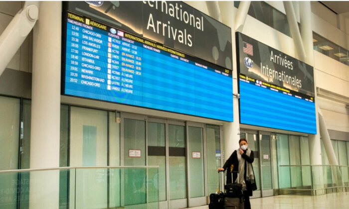 A lone passenger stands outside the International Arrivals area at Pearson Airport in Toronto on January 26, 2021. (Frank Gunn/The Canadian Press)