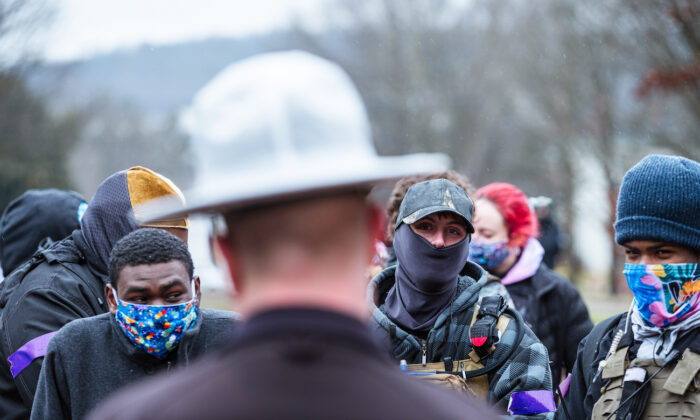 Armed members of the left-wing subsection of the militia coined the Boogaloo Boys converse with Kentucky State troopers outside of the Capitol in Frankfort, Kentucky, on Jan. 17, 2021. (Jon Cherry/Getty Images)