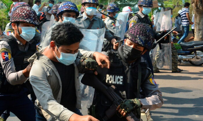 A demonstrator is detained by police officers during a protest against the military coup in Mawlamyine, Burma, on Feb. 12, 2021. (Than Lwin Times/Handout via Reuters)