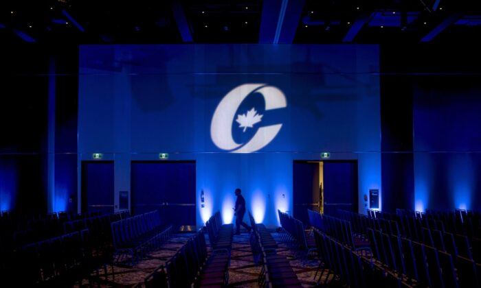A man is silhouetted walking past a Conservative Party logo before the opening of the Party's national convention in Halifax, on Aug. 23, 2018. (Darren Calabrese/The Canadian Press)