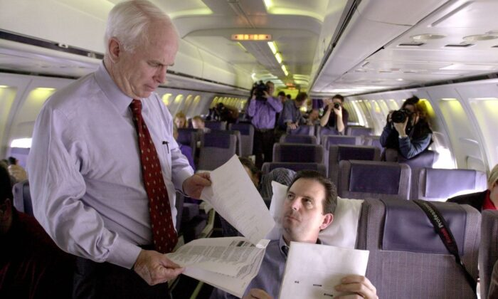 Late Arizona Senator John McCain (L) looks over some documents with campaign advisor John Weaver (R) while flying from Virginia Beach to Bismarck, North Dakota 28 February, 2000. (Roberto Schmidt/AFP via Getty Images)