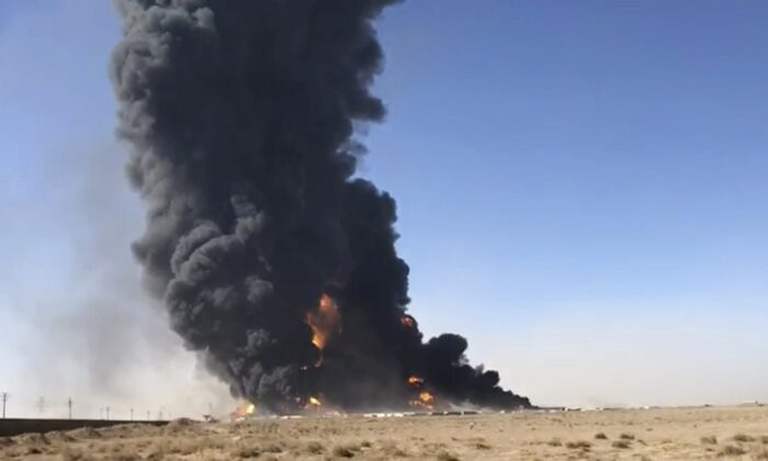 In this still image taken from video, smoke rises from fuel tankers at the Islam Qala border with Iran, in Herat Province, west of Kabul, Afghanistan on Feb. 13, 2021. (AP Photo)