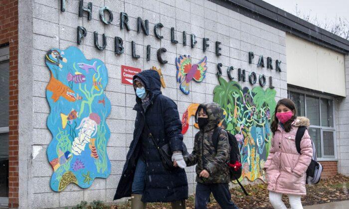 A family walks past Thorncliffe Park Public School in Toronto on Dec. 4, 2020. (The Canadian Press/Frank Gunn)
