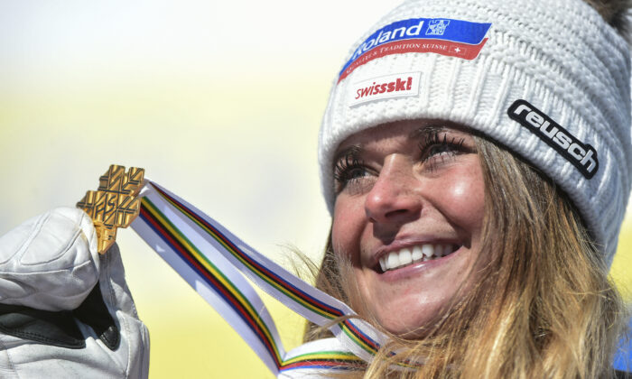 Switzerland's Corinne Suter holds the gold medal on the podium after the women's downhill, at the alpine ski World Championships in Cortina d'Ampezzo, Italy, on Feb. 13, 2021. (Marco Tacca/AP Photo)