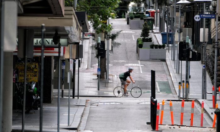 A man cycles along a street in Melbourne, Australia, on Feb. 13, 2021. (Luis Ascui/Getty Images)