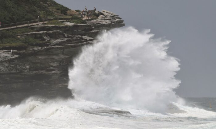 People watch the spray as large seas pound the coast near Tamarama Beach in Sydney on March 6, 2017. (William West/AFP via Getty Images)