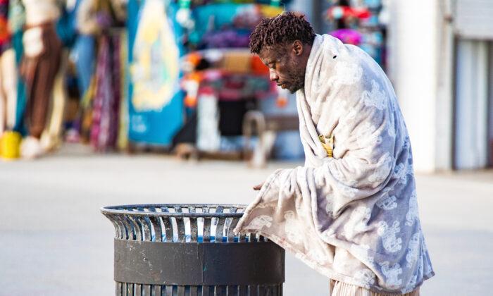 A homeless man looks in a trash can near the boardwalk at Venice Beach in Los Angeles on Jan. 27, 2021. (John Fredricks/The Epoch Times)