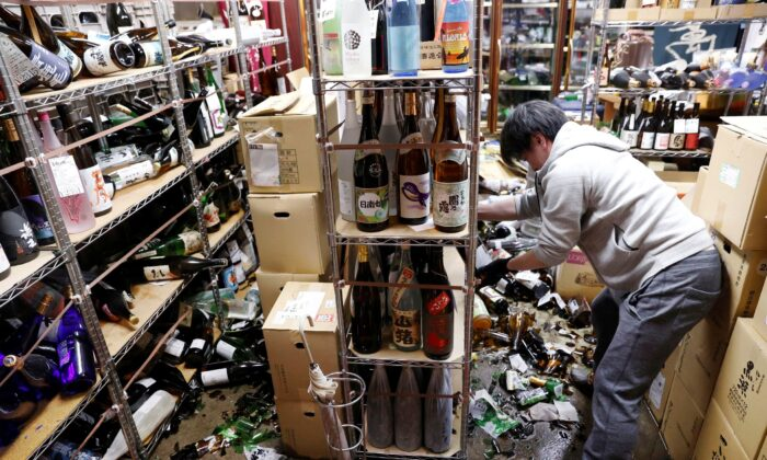 A liquor shop's manager clears the damaged bottles following an earthquake in Fukushima, northeastern Japan, on Feb. 13, 2021. (Jun Hirata/Kyodo News via AP)