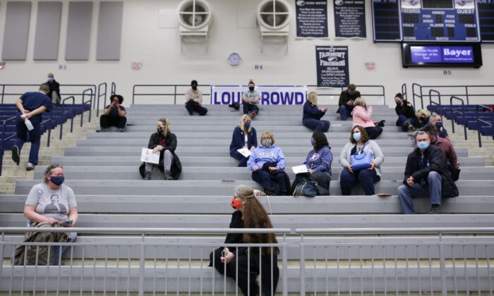 Educational staff at Kettering City Schools sit in bleachers after receiving their COVID-19 vaccine as a part of Ohios Phase 1B vaccine distribution in Dayton, Ohio, on Feb. 10, 2021. (Megan Jelinger/AFP via Getty Images)