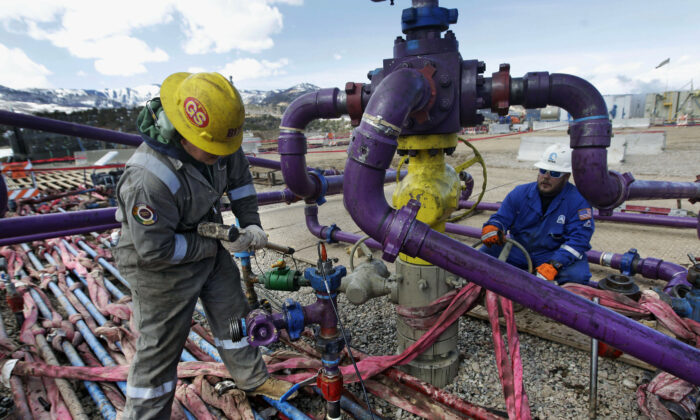 Workers tend to a well head during a hydraulic fracturing operation outside Rifle, Colo., on March 29, 2013. (Brennan Linsley/AP Photo)