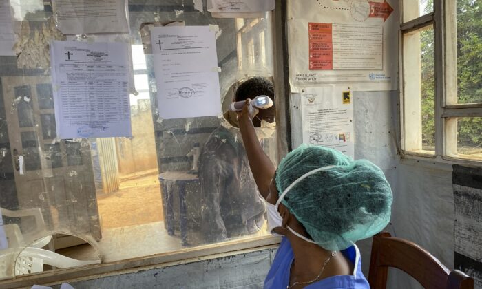 A medical worker checks a person's temperature at the Matanda Hospital in Butembo, where the first case of Ebola died, in the North Kivu province of Congo, on Feb. 11, 2021. (Al-hadji Kudra Maliro/AP Photo)