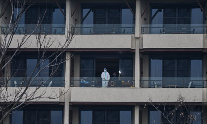 A health worker waits for members of the World Health Organization (WHO) team investigating the origins of the COVID-19 on a balcony at Wuhan Hilton Optics Valley hotel in Wuhan, China, on Feb. 6, 2021. (HECTOR RETAMAL/AFP via Getty Images)