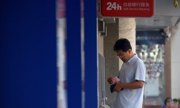 A man counts money in front of an automatic teller machine at the entrance of a bank in Beijing on Aug. 13, 2015.  (WANG ZHAO/AFP via Getty Images)