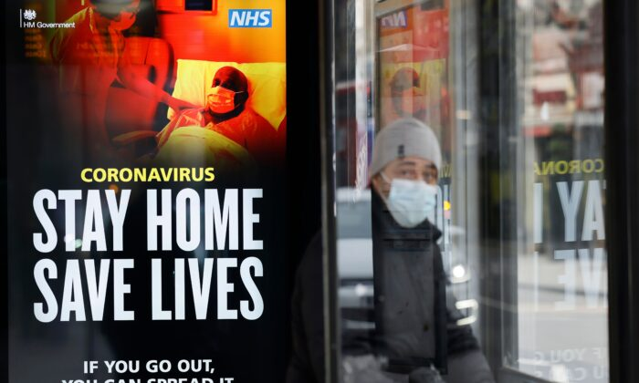 "A commuter wears a facemask as he sits in a bus shelter with NHS signage promoting ""Stay Home, Save Lives"" in Chinatown, central London, on Jan. 8, 2021. (Tolga Akmen /AFP via Getty Images)"