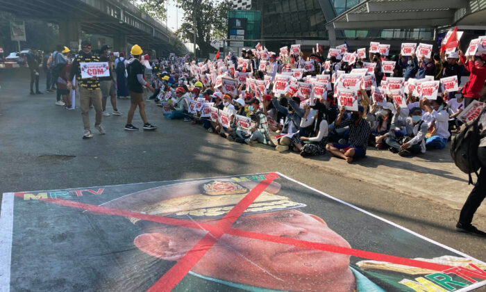 A large image that has an X mark on the face of Commander in chief Senior Gen. Min Aung Hlaing, also chairman of the State Administrative Council, lies on a road as anti-coup protesters gather outside the Hledan Centre in Yangon, Burma, on Feb. 14, 2021. (AP Photo)