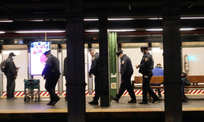 New York Police Department officers walk down a platform in the New York subway system as the outbreak of the coronavirus continues in New York, on April 13, 2020. (Lucas Jackson/Reuters)