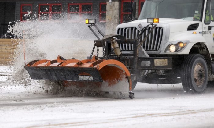 A City of Tulsa snow plow clears Harvard Ave. near 16th street in Tulsa, Okla., on Feb. 14, 2021. (John Clanton/Tulsa World via AP)