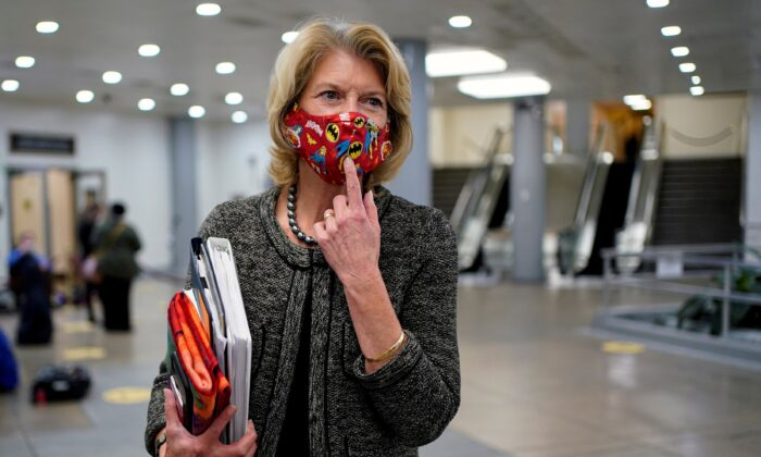 Sen. Lisa Murkowski (R-Alaska) points to her a Batman mask as she departs after House impeachment managers rested their case in impeachment trial of former President Donald Trump, on charges of inciting the deadly attack on the U.S. Capitol, on Capitol Hill in Washington on 11, 2021. (Joshua Roberts/Reuters)