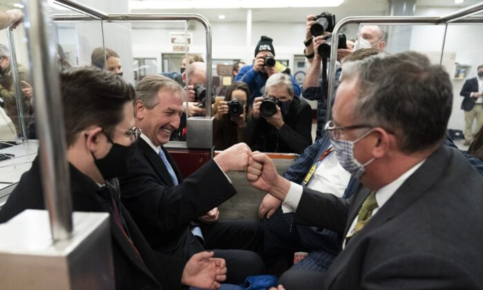 Former President Donald Trump lawyer Michael van der Veen (2nd L) celebrates with colleagues after the acquittal of Trump, on the Senate subway in Washington on Feb. 13, 2021. (Alex Brandon/AP Photo)