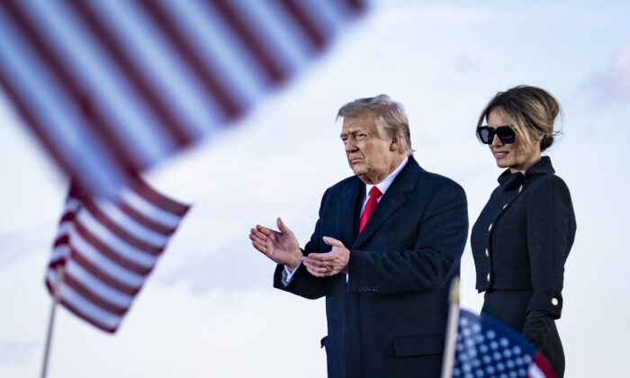 President Donald Trump and First Lady Melania Trump on stage after speaking to supporters at Joint Base Andrews before boarding Air Force One for his last time as President in Joint Base Andrews, Md., on Jan. 20, 2021. (Pete Marovich/Pool/Getty Images)