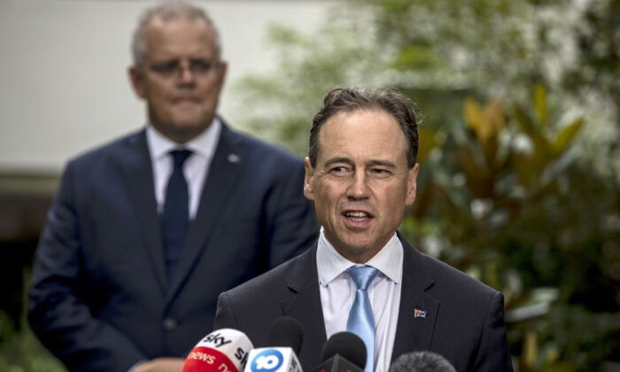 Health Minister Greg Hunt speaks as Prime Minister Scott Morrison looks on at the news conference at the CSL facility on February 12, 2021 in Melbourne, Australia. (Diego Fedele/Getty Images)