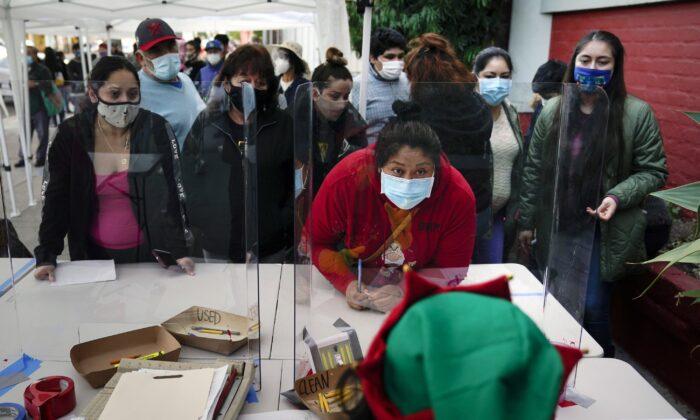 People check in at a food bank held at Los Angeles Boys & Girls Club in the Lincoln Heights neighborhood of Los Angeles on Dec. 17, 2020. (Jae C. Hong/AP Photo)