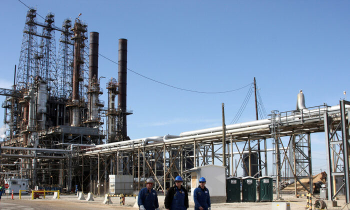Refinery workers walk inside the LyondellBasell oil refinery in Houston, Texas, on March 6, 2013. (Donna Carson/Reuters)