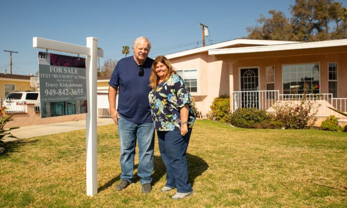 John Peterson and his wife stand next to a for-sale sign on their lawn in Garden Grove, Calif., on Feb. 7, 2021. (John Fredricks/The Epoch Times)
