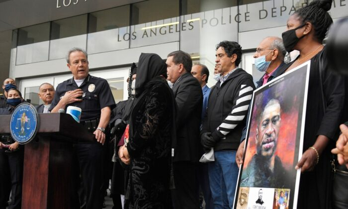 Los Angeles police chief Michel Moore (L) speaks as someone holds up a portrait of George Floyd during a vigil with members of professional associations and the interfaith community at Los Angeles Police Department headquarters in Los Angeles, Calif., on June 5, 2020. (Mark J. Terrill/ File/AP Photo)