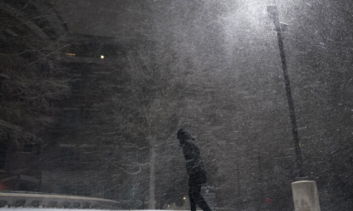 A woman walks through falling snow in San Antonio on Feb. 14, 2021. (Eric Gay/AP Photo)