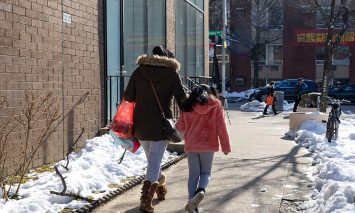 A woman and a little girl walk on the street in Flushing, New York on Feb. 10, 2021. (Chung I Ho/The Epoch Times)