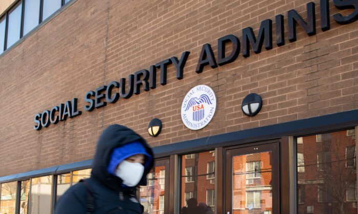A woman wearing a protective face mask walks past a Social Security Administration during the CCP virus pandemic in Flushing, N.Y., on Feb. 10, 2021. (Chung I Ho/The Epoch Times)