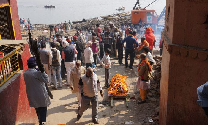 A corpse decked in marigold flowers waits for its turn on the pyre on the ground at the Manikarnika Ghat in Kashi on Feb. 12, 2021. (Venus Upadhayaya/Epoch Times)