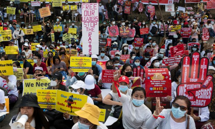 Demonstrators holding placards sit during a protest against the military coup outside the U.S. embassy in Yangon, Burma on Feb. 16, 2021. (Stringer/Reuters)
