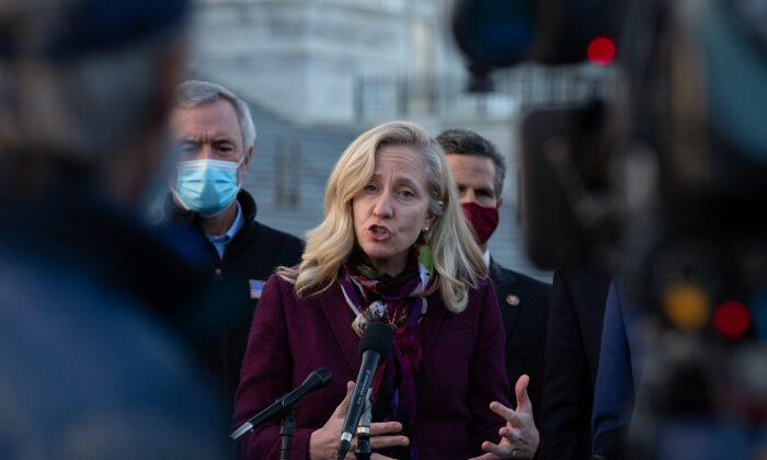 Rep. Abigail Spanberger (D-Va.) speaks at the podium standing with members of the Problem Solvers Caucus in a press conference outside the U.S. Capitol on Dec. 21, 2020. (Cheriss May/Getty Images)