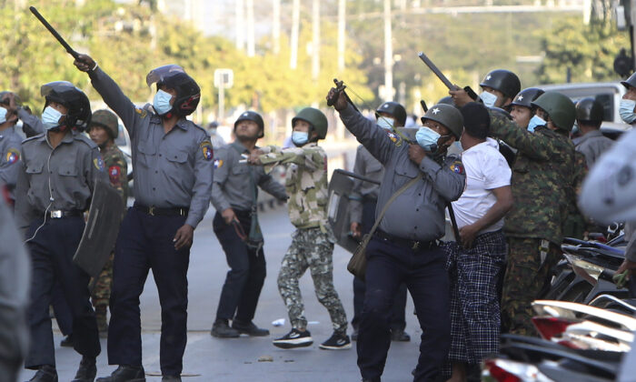 A policeman aims a slingshot toward an unknown target during a crackdown on anti-coup protesters holding a rally in front of the Myanmar Economic Bank in Mandalay, Burma (also known as Myanmar), on Feb. 15, 2021. (AP Photo)