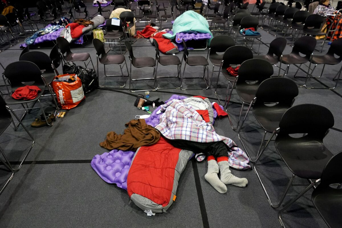 People seeking shelter from below freezing temperatures rest inside a church warming center Tuesday, Feb. 16, 2021, in Houston.