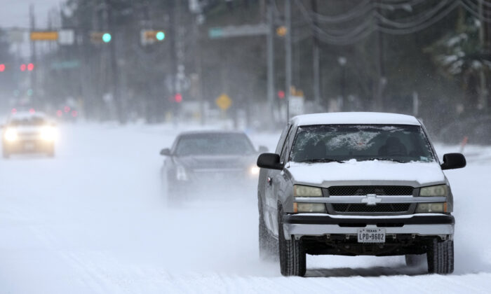Vehicles drive on snow and sleet covered roads in Spring, Tex. on Feb. 15, 2021. (David J. Phillip/AP Photo)