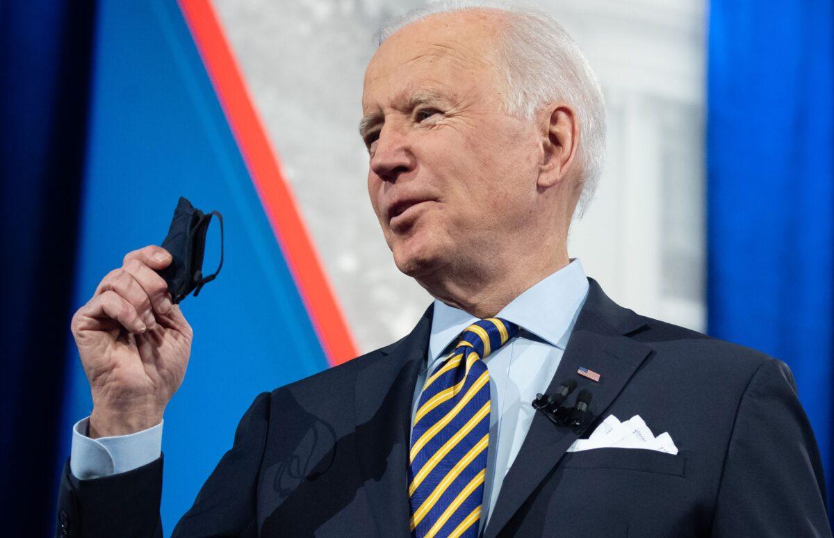 U.S. President Joe Biden holds a face mask