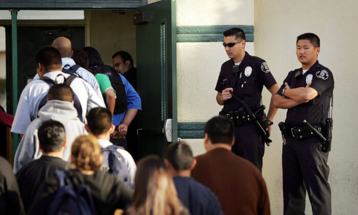 Los Angeles School Police officers watch students lining up to pass through a security check point at Thomas Jefferson High School in Los Angeles, Calif., on April 21, 2005. (David McNew/Getty Images)