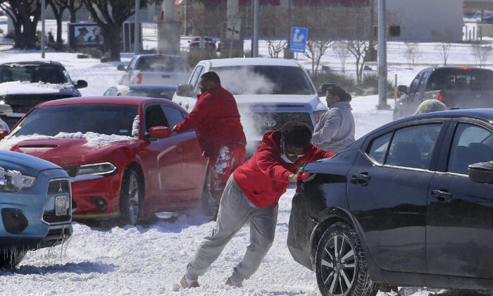 People push a car free after spinning out in the snow in Waco, Texas, on Feb. 15, 2021. (Jerry Larson/Waco Tribune-Herald via AP)