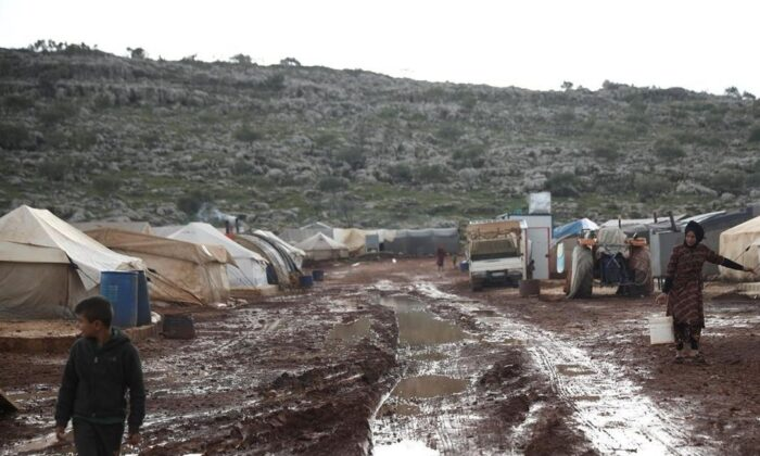 Syrian refugees walk through a camp for the displaced muddied by recent rains near the village of Kafr Aruq, in Idlib province, Syria, on Jan. 28, 2021. A United Nations rights' advocate and Human Rights Watch Canada say the Trudeau government isn't living up to its new international campaign against arbitrary detention because it is abandoning 25 Canadian children trapped in northern Syria.  (Ghaith Alsayed/AP/The Canadian Press)