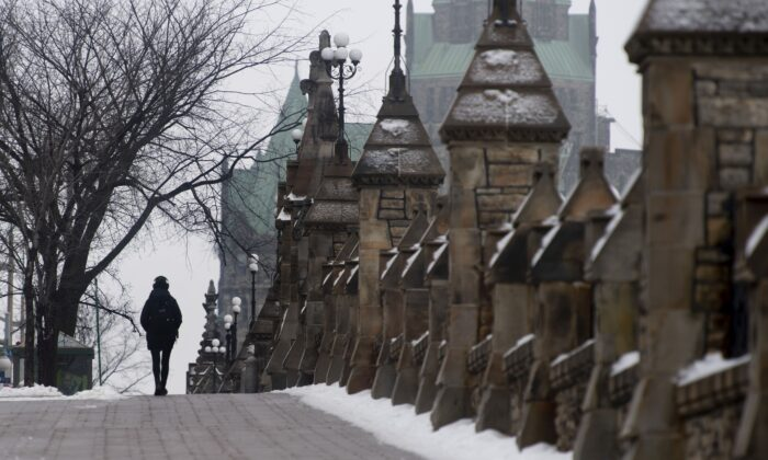 A person walks along the sidewalk next to Parliament Hill in Ottawa on Jan. 14, 2021 (The Canadian Press/Adrian Wyld)