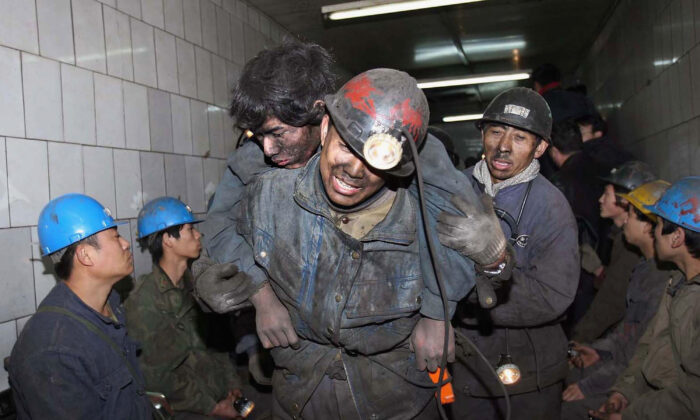 Rescuers assist miner Feng Yin after he was trapped following a blast accident that occured at Dongfeng Coal Mine on Nov. 28, 2005 in suburb of Qitaihe City of Heilongjiang Province, northeast China. (China Photos/Getty Images)