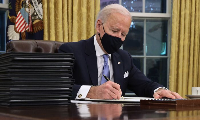 President Joe Biden signs a series of executive orders at the Resolute Desk in the Oval Office just hours after his inauguration in Washington on Jan. 20, 2021. (Chip Somodevilla/Getty Images)